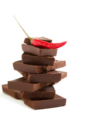 Red chili pepper on stack of dark chocolate pieces on white back