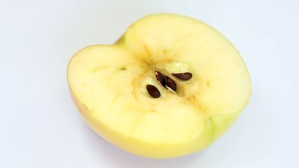 Sliced fresh yellow apple rotating on white