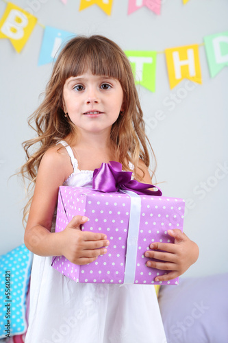 Little girl with gift in room on grey wall background
