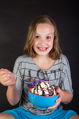 A happy young girl about to eat some ice cream