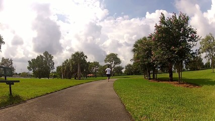 sport man in white running in park.