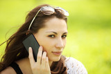 Young beautiful woman in city park speaks by mobile phon