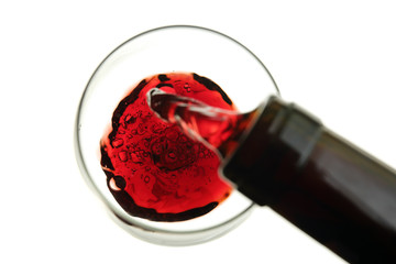 red wine being poured into a glass isolated on white