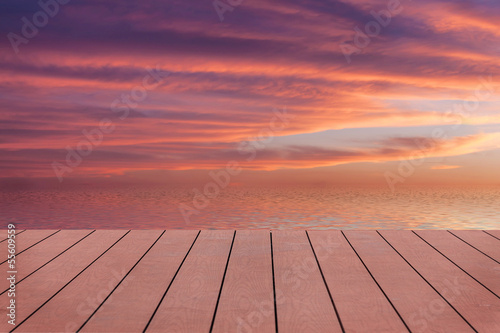 Sunset with clouds reflected in water. View from wooden pier.