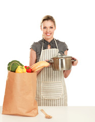 Woman in apron  holding a pan with grocery bag
