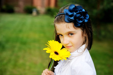 Young girl in school uniform posing with flowers