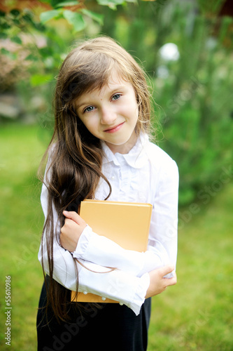 Young girl in school uniform holding a book