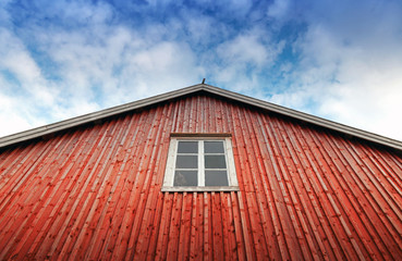 Red wooden wall with window above blue cloudy sky