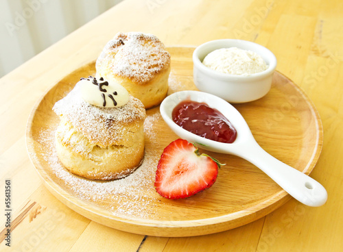 Scone spread with cream and strawberry jam
