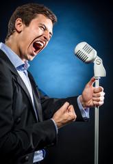 Man in elegant black jacket and blue shirt singing