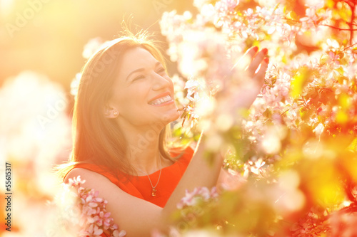 beautiful young woman in spring garden near blooming tree