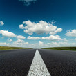 asphalt road to horizon in deep blue cloudy sky