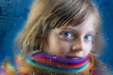 rainy autumn - face of a little girl behind a dewy window