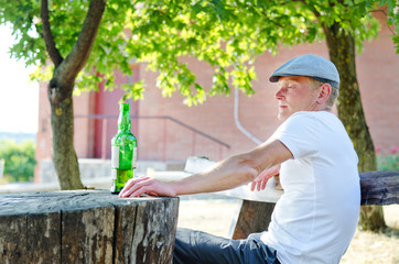Lonely man sitting with a bottle of alcohol