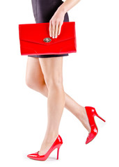 Beautiful womanish feet in red shoes and mini bag