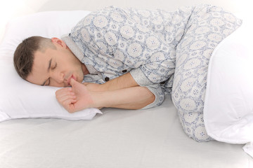 Big baby in pajamas. Side view of infant adult man sleeping on t