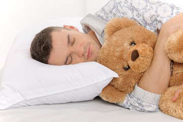Big baby with Teddy Bear. Infant adult man sleeping with his ted