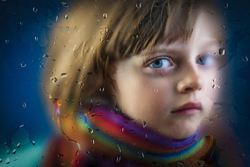 rainy day -  a little girl behind a dewy window