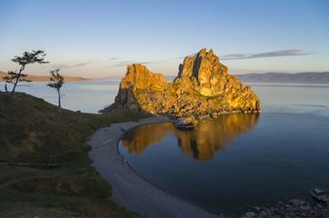 Shaman Rock in the rays of the rising sun. Olkhon Island, Baikal