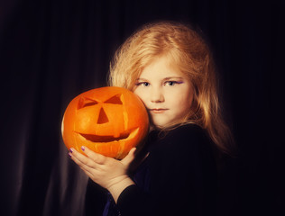 little witch with pumpkin on dark background