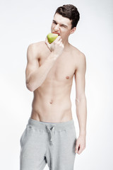 young man eating green apple