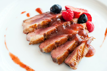 Grilled duck breast with sweet red fruit dressing.