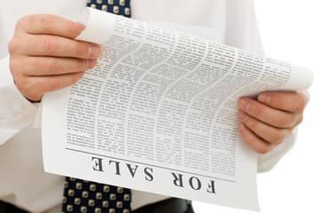 Businessman reading sales ads