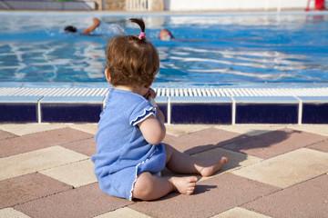 Bebé sentada junto a la piscina viendo a los bañistas