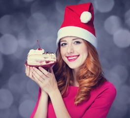 Redhead girl in christmas hat with cake