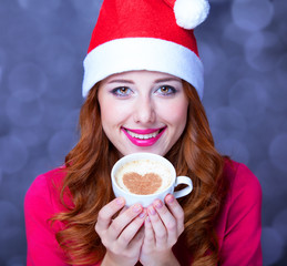 Redhead girl in christmas hat with cup of coffee