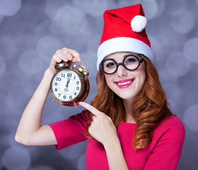 Redhead girl in christmas hat with clock