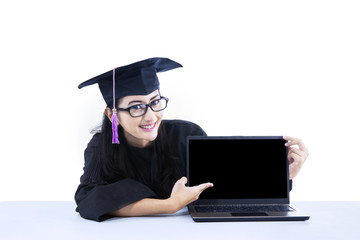 Female graduate pointing at empty laptop screen