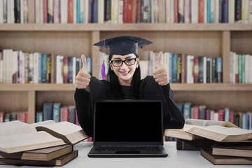Graduate woman giving thumbs up in library