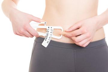 Woman measuring her body fat on adbomen using caliper