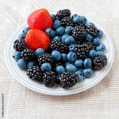 Small plate with fresh summer berries - strawberry, blueberry an