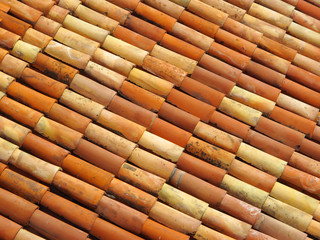 Roof tiles in different colors from yellow to red.