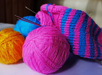 Three woollen balls, knitting-needles and half-knitted sock