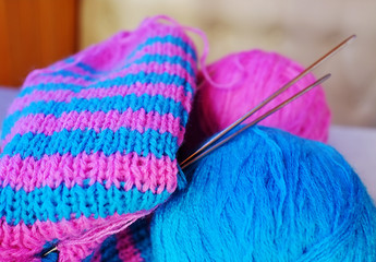 Two woollen balls, knitting-needles and half-knitted sock
