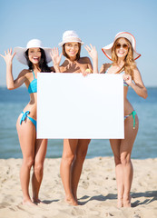 girls with blank board on the beach