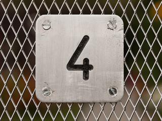 Hausnummer 4 aus Metall an einem Metallzaun