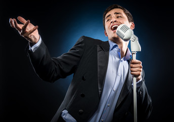 Man in elegant black jacket and blue shirt singing