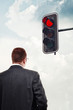 Businessman in front of red traffic light