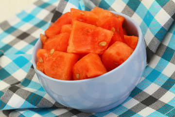 Watermelon cubes in blue bowl on checkered cloth
