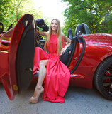 Young woman in red dress siting in a  sports car