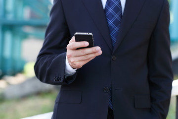 Close up of the hands of the businessman with a mobile phone