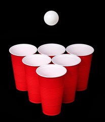 Beer pong. Red plastic cups and ping pong ball over black
