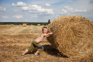 Boy with bale of straw