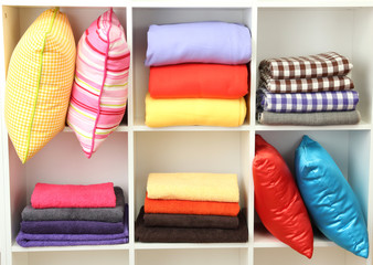 Bright pillows, towels and plaids on shelves, isolated on white
