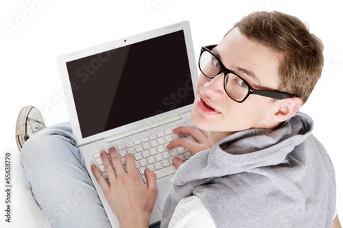 Young happy man with laptop sitting on the floor