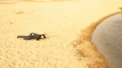 Businessman Crawling in Desert Reaching Water Success Concept